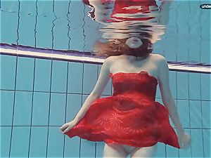 crimson dressed teenager swimming with her eyes opened